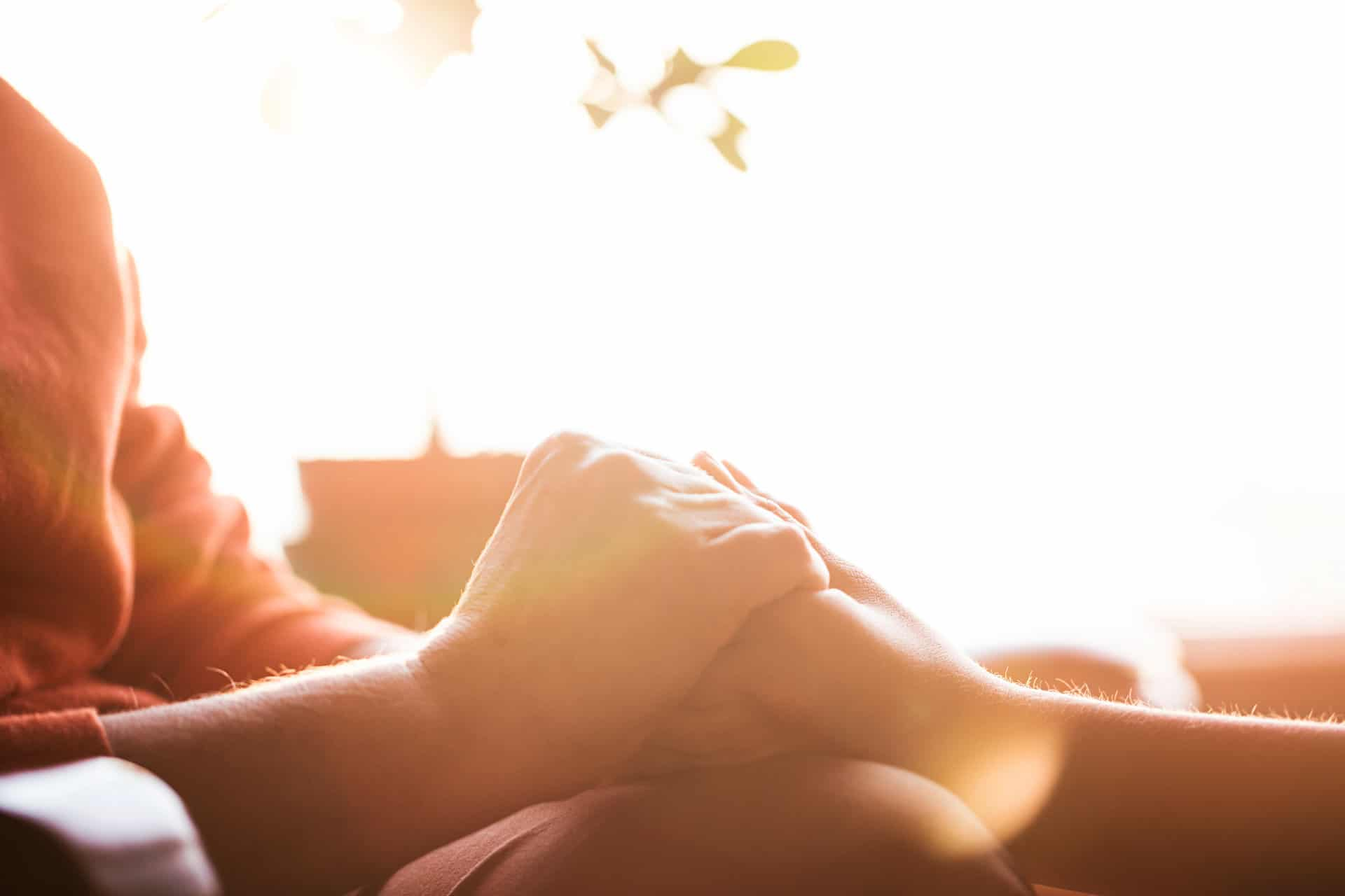 Close-up image of two people holding hands in a room with bright sunlight filtered through the window