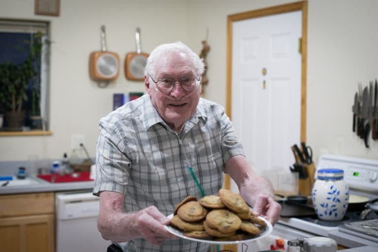 Ray's chocolate chip cookies are legendary. Here he is shown serving a plate of cookies with a huge smile on his face.