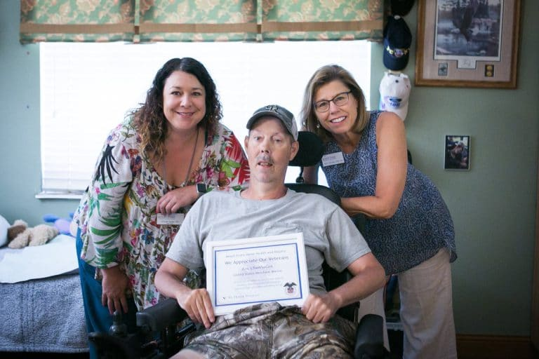 "Two health care professionals with patient in wheel chair holding a ""Veterans Appreciation"" certificate."