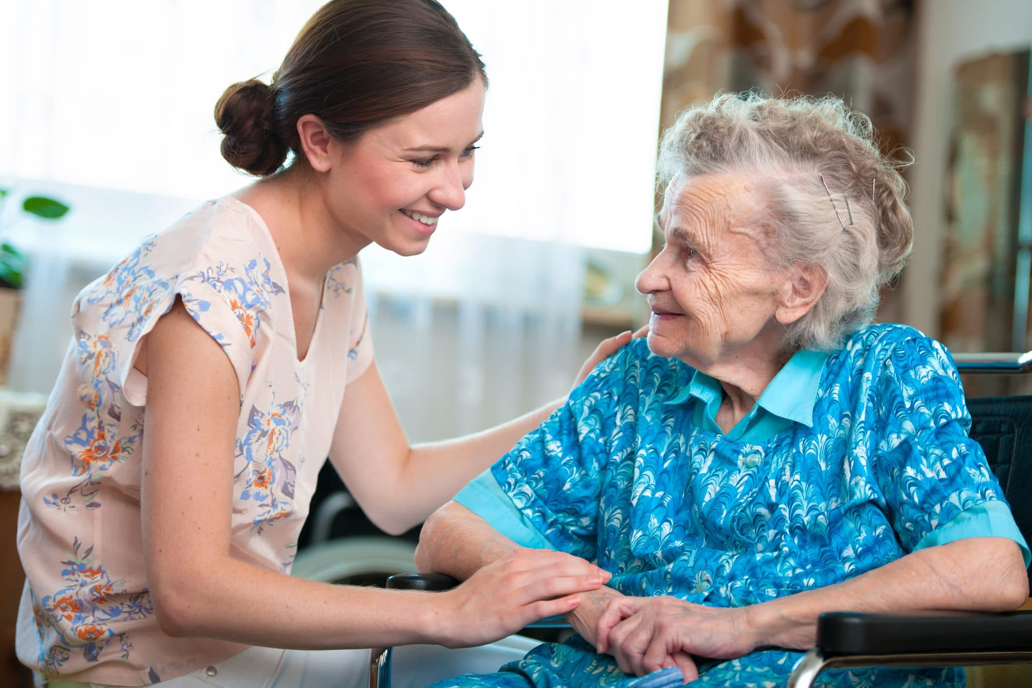 Elderly woman on wheelchair with a home health care CNA