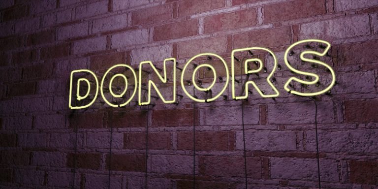 "Glowing Neon Sign with the word "" Donors"" on stonework wall wi"