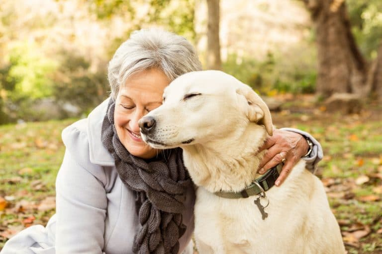 Senior woman smiling in the forest with her arms around her yellow Labrador dog