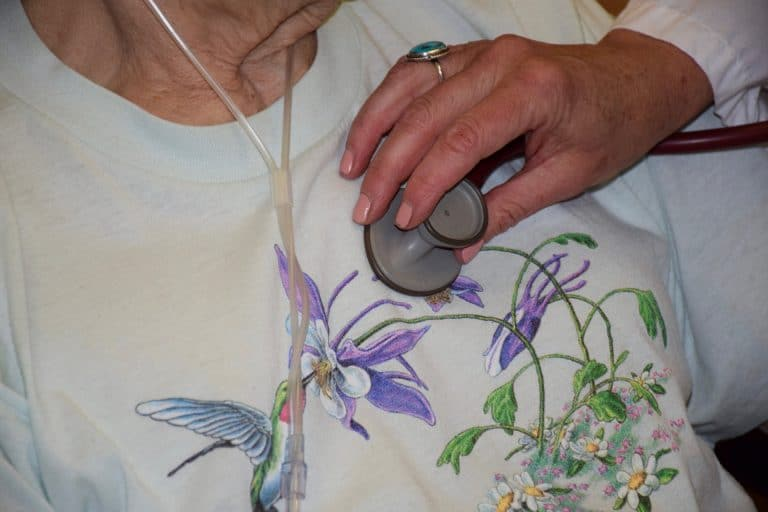 Hospice care patient wearing a purple flowered sweater getting her lungs sounds auscultated by a stethoscope