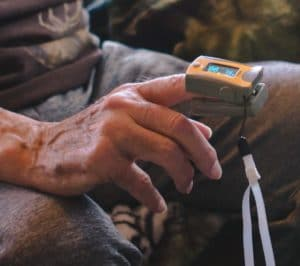 Close-up image of a pulse oximeter on a patients right index finger