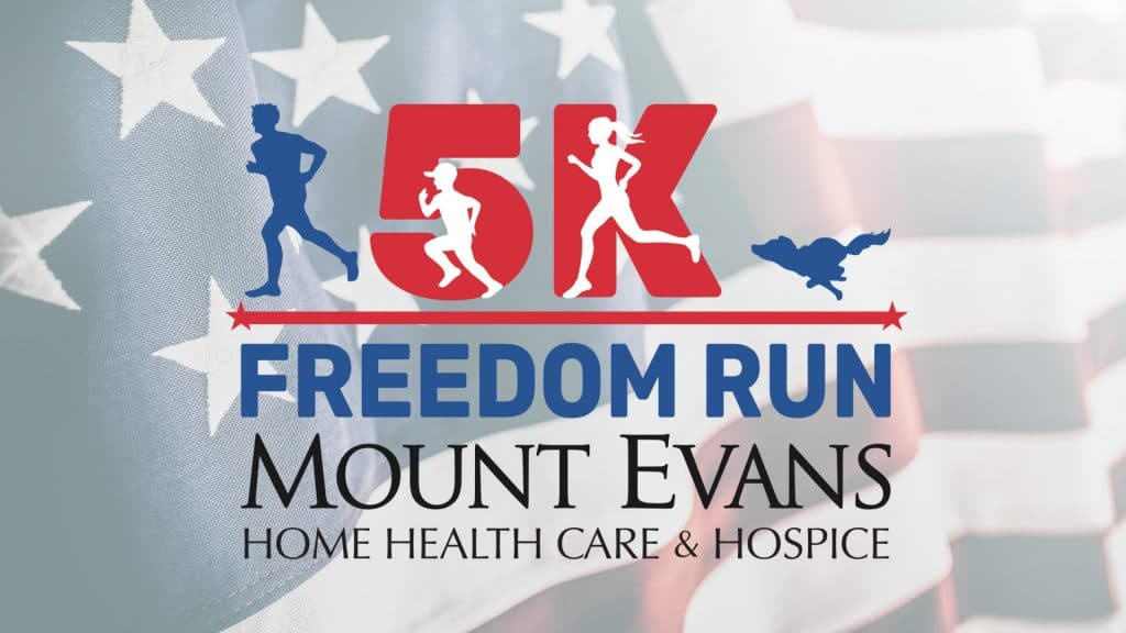 Mount Evans' Freedom Run 5k logo superimposed on top of a waving American flag