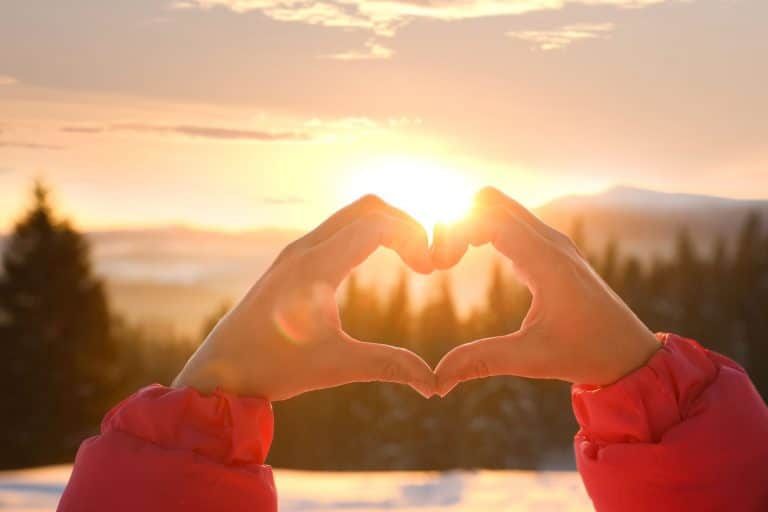 Close-up image of a person's hands forming a heart shape with a mountain sunset in the background