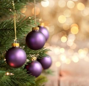 Christmas tree with purple baubles and gold lights against a bokeh background