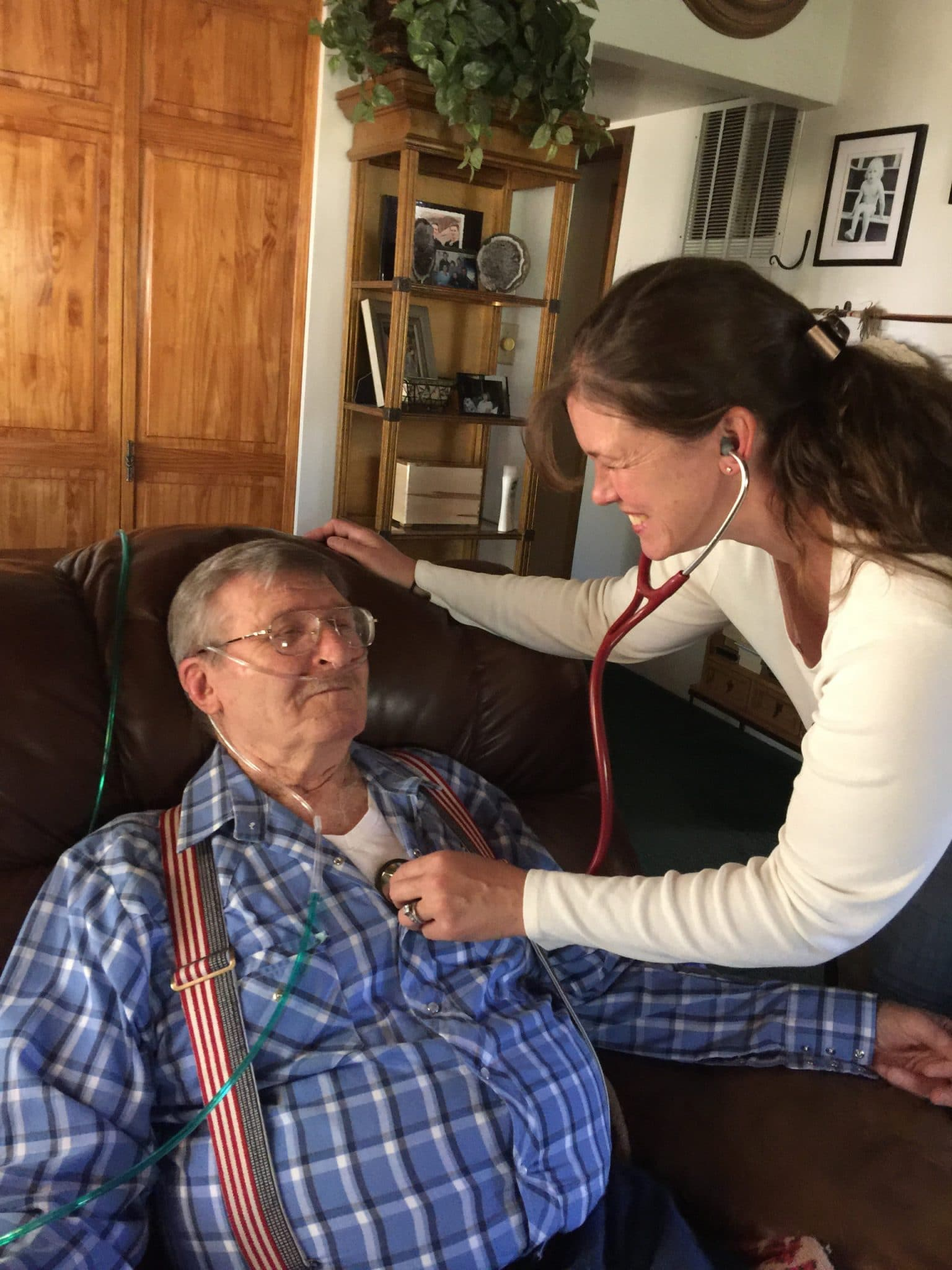 Female Mount Evans' RN with her oxygen dependent patient while she auscultates his lung sounds. Both individuals are smiling and having a good moment.