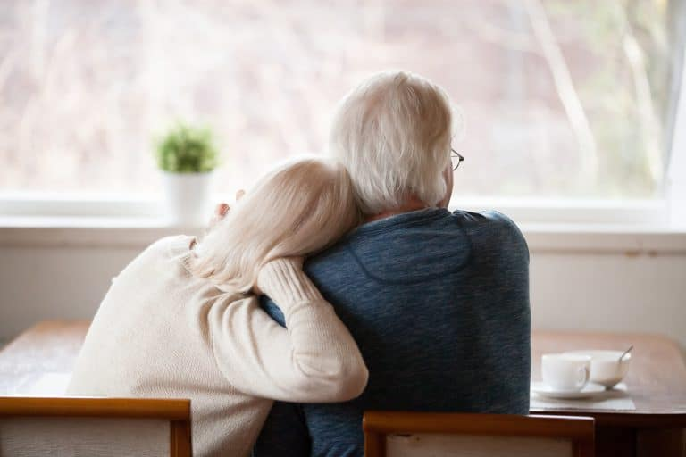 Rear view of senior grey haired couple relaxing at home looking out the window with coffee on the table