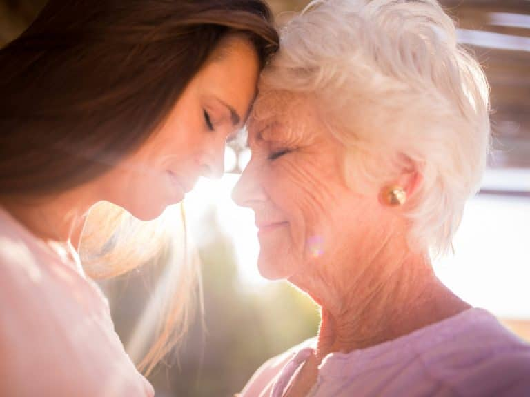 Special moment between a senior woman and her loving adult daughter standing close together outdoors with sun flare