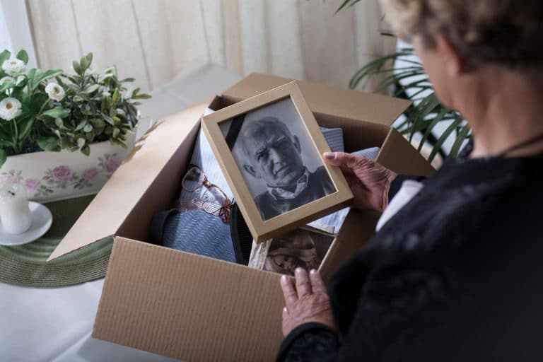 Woman is packing up belongings and memories of her deceased husband while looking a portrait photo of him