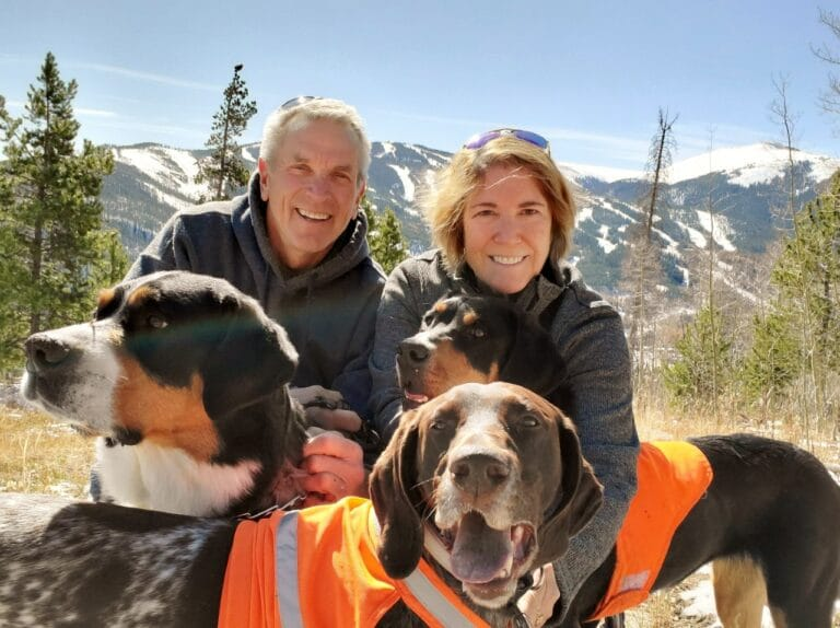 Mount Evans CEO, Keri Jaeger with husband and three dogs in mountains with ski hill in distance