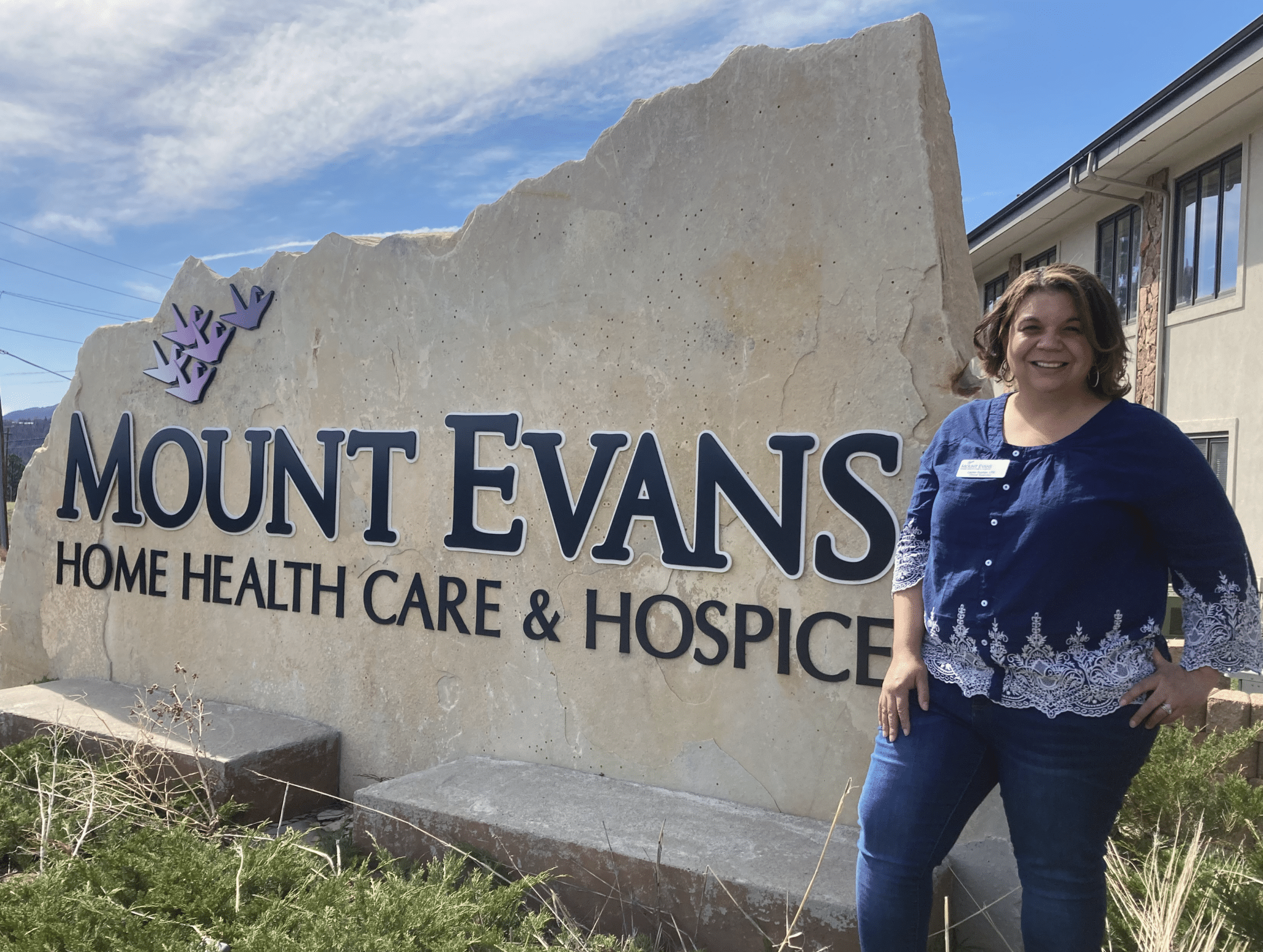 Lauren Guzman, Clinical Supervisor, LPN in front of the Mount Evans Home Health Care & Hospice sign