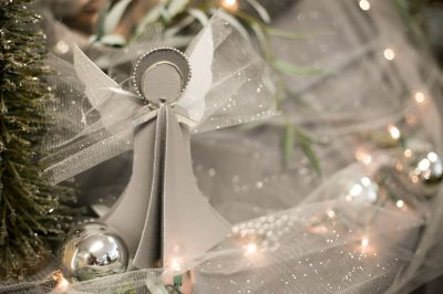 Angel Ornament with silver and white holiday lights and ornaments in the background