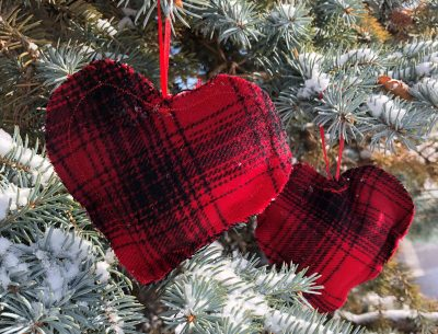 Close-up image of the hand sewn holiday hand warmers in a tartan plaid print while hanging on a snow covered pine tree