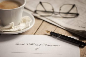 Stylized table setting of last will and testament paperwork, a cup of coffee, a pen, reading glasses, and the financial section of a newspaper