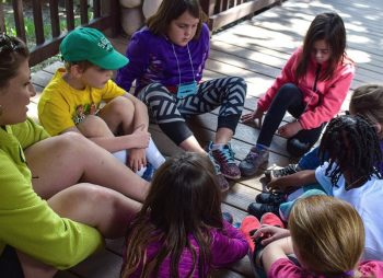 Group of seven school age girls and boys from Camp Comfort sitting in a cricle on a wooden deck along with their camp counselor